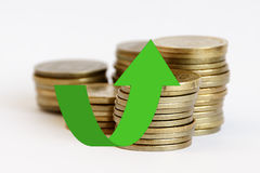 Stacks of coins with a green arrow. Up on them Stock Photo