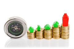 Stacks of coins, green and red home with compass. Stock Photography