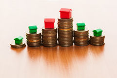 Stacks of coins, green and red home Royalty Free Stock Image