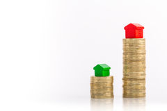 Stacks of coins with green and red home. Saving money to buy real estate or larger property Royalty Free Stock Photography