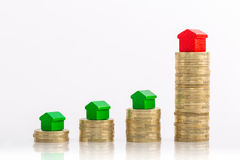 Stacks of coins with green and red homes. Saving money to buy real estate or larger property Royalty Free Stock Images