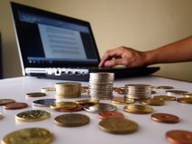Stacks of coins and a hand working on a laptop computer Royalty Free Stock Image