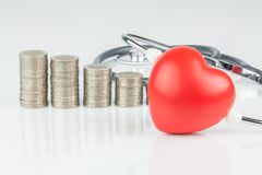 Stacks of coins and heart on white background. Stacks of coins and heart Royalty Free Stock Photography