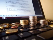Stacks of coins and a laptop computer Royalty Free Stock Photo