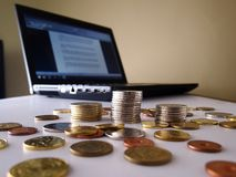 Stacks of coins and a laptop computer Royalty Free Stock Photos