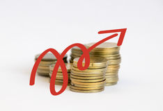 Stacks of coins with a red arrow. Up on them Royalty Free Stock Images