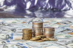 Stacks of coins on the scattered notes of one hundred dollars on a brilliant background. stock photo