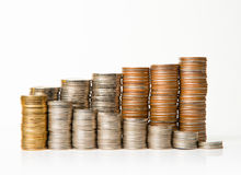 Stacks of coins on white background. Side view of stacks of coins increasing in height, on white  background Stock Image