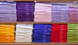 Stacks of colored terry towels on the shelves in a shop Stock Image