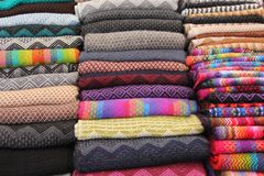Stacks of colorful fabrics at a market. Stacks of colorful fabrics are for sale at the Pisac souvenir market in the Sacred Valley, Peru stock images