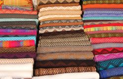 Stacks of colorful fabrics and blankets. Are for sale at the Pisac souvenir market in the Sacred Valley, Peru royalty free stock photos