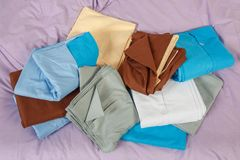 Stacks colourful bed linen textiles clothing background pile concept Stock Photo