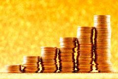 Stacks of copper coins on golden background Royalty Free Stock Images