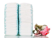 Stacks of diapers, broken piggy bank, money isolated on white. Royalty Free Stock Image