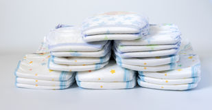 Stacks of diapers stacked in staggered rows on a white background Stock Photo