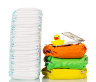 Stacks disposable and cloth diapers, money, rubber duck isolated. Stacks of disposable and cloth diapers, money, and a rubber duck isolated on white background royalty free stock photography