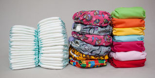 Stacks of disposable diapers and modern cloth diapers Royalty Free Stock Photo