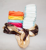 Stacks of disposable diapers and modern cloth diapers Stock Images