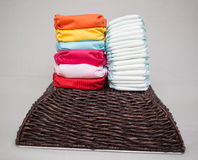 Stacks of disposable diapers and modern cloth diapers Stock Photos