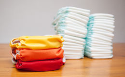 Stacks of disposable diapers and modern cloth diapers Royalty Free Stock Image