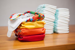 Stacks of disposable diapers and modern cloth diapers Stock Photography