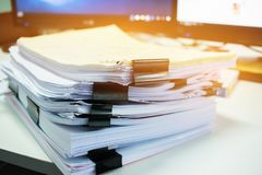 Stacks of documents files for finance of office working.Business report papers or Piles of unfinished document achieves with. Black clip paper. Concept of stock photo