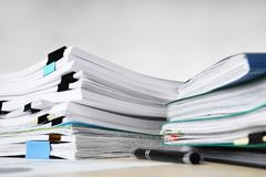 Stacks of documents on table. Against light background stock images