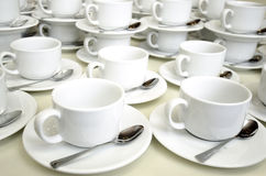 Stacks of Empty Coffee Cups. Stacks of empty white ceramic coffee cups and saucers with spoons Stock Photography