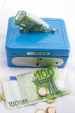 Stacks of  euro coins and banknotes in a cash box. On a white background Royalty Free Stock Image