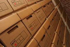 Stacks of file boxes. A background of stacked cardboard boxes in a warehouse Royalty Free Stock Image