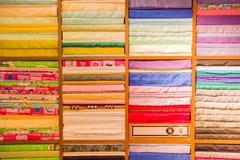 Stacks of folded clothing on the shop shelves Stock Image