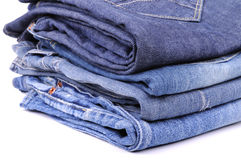Stacks of four blue jeans. On the white background Stock Photo