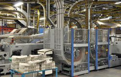 stacks of freshly printed daily newspapers and machines in a large printing plant