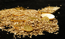 Stacks of gold. A pile of gold bullion, ingots, coins and nuggets on a black background Stock Photos