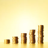 Stacks of gold coins. Increasingly higher stacks or piles of gold coins on a yellow background Stock Image