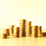 Stacks of gold coins. Increasingly higher stacks or piles of gold coins on a yellow background Royalty Free Stock Image