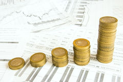Stacks of coins, graph, diagram. Stacks of gold coins like increasing columns over different paper documents background. Earnings or saving graph (diagram Stock Photo