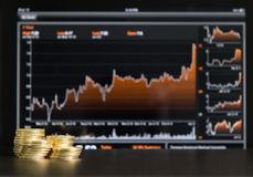 Stock market. Stacks of gold coins and a stock market chart in the background Stock Photo