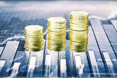 Stacks of gold coins on the table with business graph. Close up Stock Image