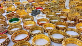 Display of gold bracelets for sale on white cloth. Stacks of gold colored bracelets spreaded on white table cloth Royalty Free Stock Images