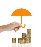 Stacks of golden coins covered by paper umbrella. Insurance concept Royalty Free Stock Image