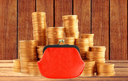 Stacks of golden coins and red purse on wooden table background Royalty Free Stock Image