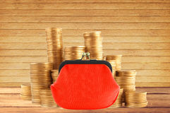 Stacks of golden coins and red purse on wooden table background Stock Images