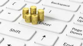 Stacks of golden coins on white  laptop Stock Photography