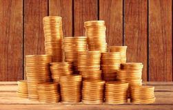 Stacks of golden coins on wooden table Royalty Free Stock Photos