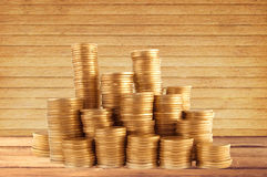 Stacks of golden coins on wooden table background Royalty Free Stock Photos