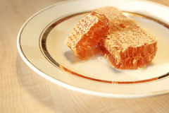 Stacks of honey comb on a plate on wooden table Stock Photo