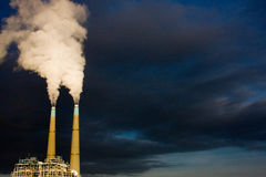 Stacks II. The sun illuminates a power plant in late afternoon while dark clouds roll in behind it Stock Images