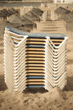 Stacks of loungers and thatched umbrellas on a sandy beach of Estoril Royalty Free Stock Photos