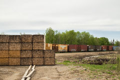 Stacks of lumber and rail cars Stock Photos